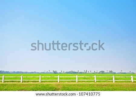 White fence and green grass on clear blue sky