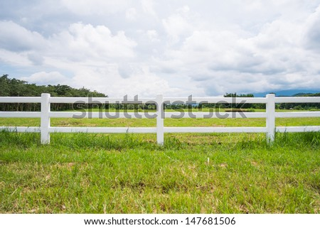 white fence in farm field and overcast sky #147681506
