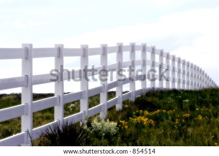 White fence line disappearing over a green hill (soft focus) - can represent goals, obstacles, nature, country living, etc.