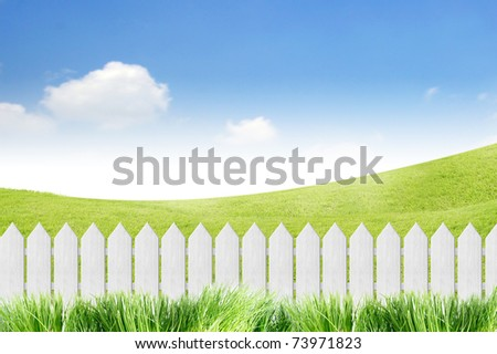 White fence with grass on clear blue sky - stock photo