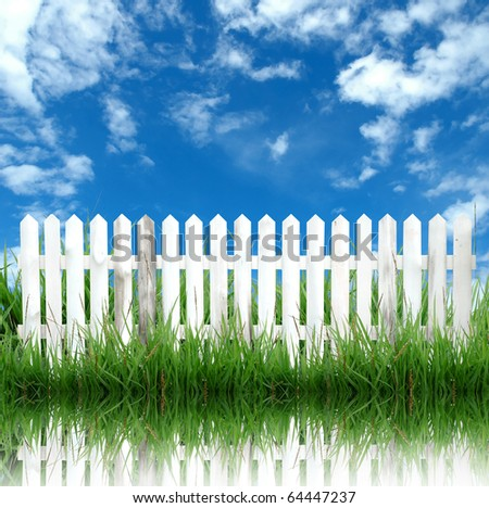 white fence with green grass and blue sky - stock photo