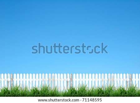 white fence with green grass and blue sky