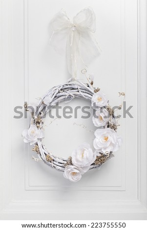 White festive twig wreath of dried vine, painted white and decorated with white paper flowers