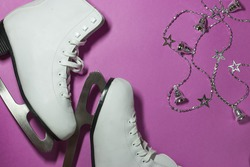 white figure skates and silver garland of bells and stars on a pink background