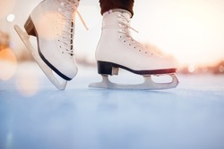 White figure skates on winter ice rink with blurry bokeh background.