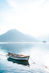 White fishing boat on calm water against the backdrop of mountains in the fog.