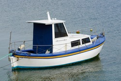 white fishing motor boat anchored in the sea