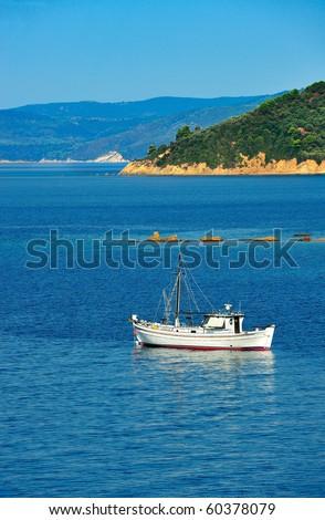 White fishing trawler anchored among islands of the Aegean Sea