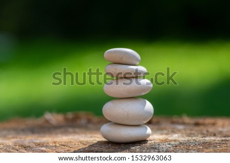 White five stones cairn in daylight, poise light pebbles on wooden stump in front of green natural background, zen like sculpture, simplicity, harmony and balance