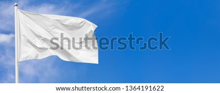 White flag waving in the wind on flagpole against the sky with clouds on sunny day, banner, closeup #1364191622