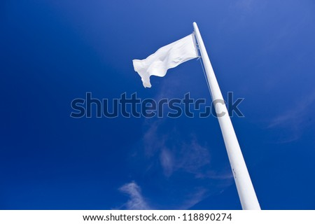 White flapping flag on blue sky.