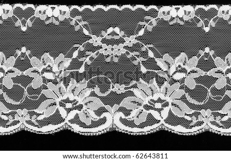 White floral lace on a black background.
