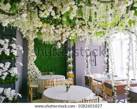 White floral wedding theme decorated with a lot of white flowers and table and sofa with grey wall