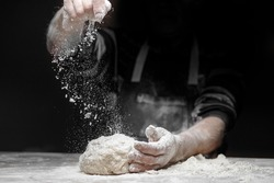 White flour flies in air on black background, pastry chef claps hands and prepares yeast dough for pizza pasta.