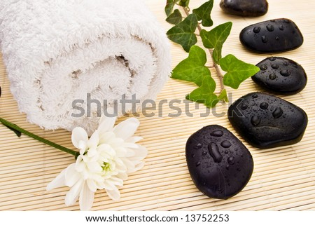 white flower towel ivy and spa stones on bamboo board