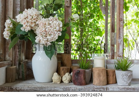 White flower vase and small succulent plants with decoration items placed on a wooden shelf near the windows in rustic atmosphere.