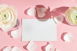 White flowers and ranunculus petals in a glass vase, with a paper card on pink background with hard light. Spring, summer, bloom. Mockup. Copyspace.