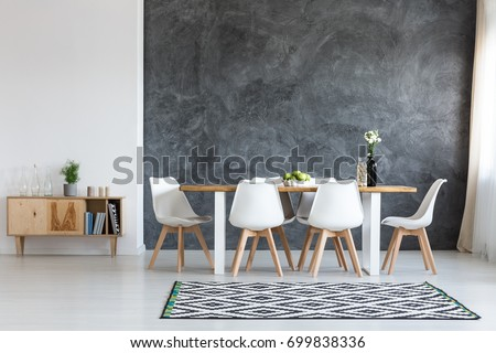 White flowers in black vase next to glass container with wine corks on dining table #699838336