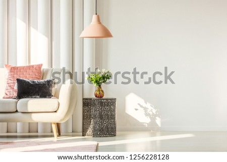 White flowers on glass vase on stylish table next to white sofa with pastel pink and black velvet pillows