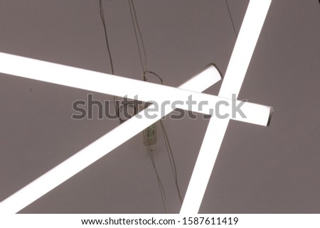 White fluorescent lamps suspended in a bright room create a picture.