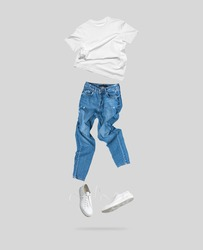 White flying cotton T-shirt, blue jeans, white leather sneakers isolated on gray background. Clean white Unisex T-shirt. Branding clothes. Mock up for your design. Spring Summer Women's Clothing
