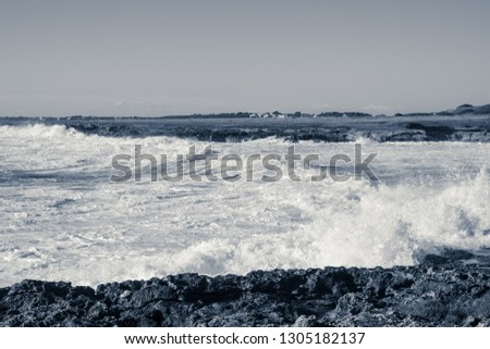 White foam created by the waves of the sea that hurl themselves against the rocky coast of Salento on a day of strong wind of Scirocco, monochrome picture.