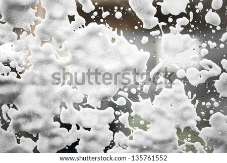 White foam drops on the wet window as it is going to be cleaned