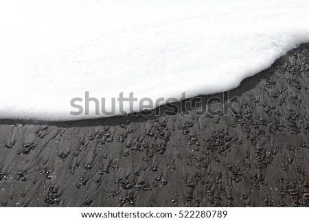 white foam on black beach in Iceland #522280789