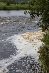 White foam pollution in a river contaminating the environment. Contaminated water swirling in an eddy