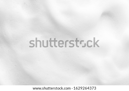 White foam texture close up background. Soapy substance with bubbles backdrop. Creamy grainy macro. Shower gel, washing liquid smears wallpaper. Cosmetic product foamy smudges top view