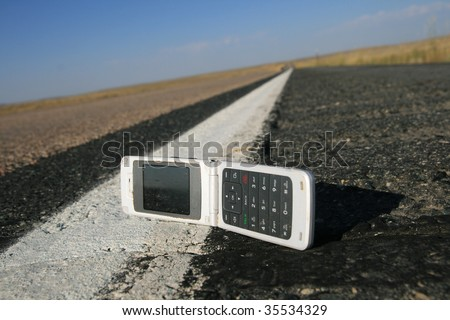 white fold up cell phone dropped on the roadside