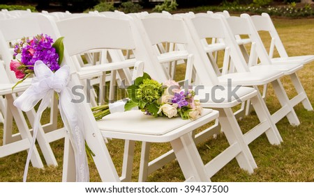 White Folding Chairs At An Outdoor Wedding With Flowers Stock ...