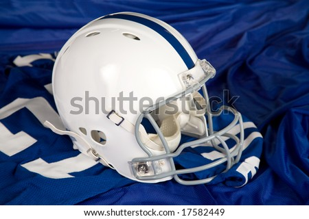 white football helmet with blue stripe sitting on a blue jersey with number 27