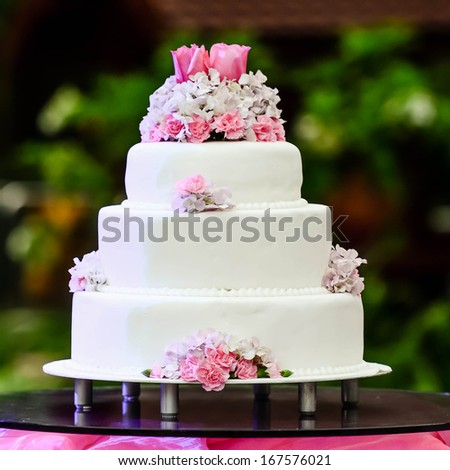 White four tiered wedding cake on table