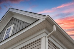 White frame gutter guard system, with gray horizontal and vertical vinyl siding fascia, drip edge, soffit, on a pitched roof attic at a luxury American single family home dramatic sunset sky