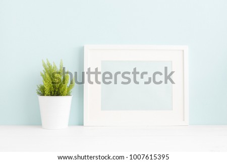 White frame mock up and a plant on a book shelf.