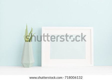 White frame mock up on a book shelf in modern interior. Bright pastel colors.