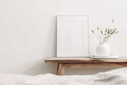 White frame mockup on vintage wooden bench, table. Modern white ceramic vase with dry Lagurus ovatus grass and marble tray. Blurred beige linen blanket in front, Scandinavian interior.