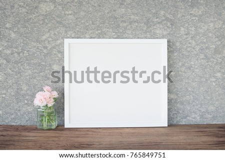 White frame with pink flower in vase on wooden shelf