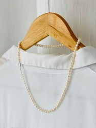 White freshwater pearl necklace on wooden hanger