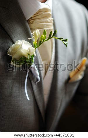 White fressia boutonniere on groom's suit - stock photo
