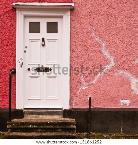 White front door in a pink wall