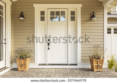 White front door with small square decorative windows and flower pots #507466978