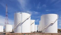 White fuel storage tank against blue sky