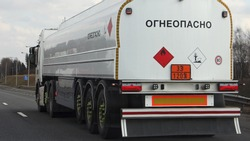 White fuel truck with 33-1203 dangerous class sign and FLAMMABLE inscription in Russian on barrel drive on suburban asphalt highway road at spring day, rear side view - ADR liquid hazardous delivery