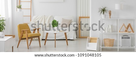 White furniture with wooden elements in monochromatic living room interior with yellow armchair, sofa and monstera leaf on a coffee table #1091048105