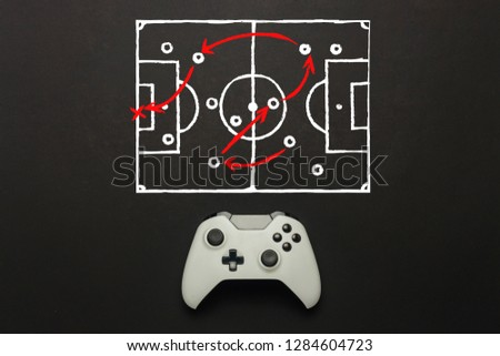 White gamepad on a black background. Added a soccer field scheme. Tactics of the game. Concept game of football on the console, computer games. Flat lay, top view. #1284604723