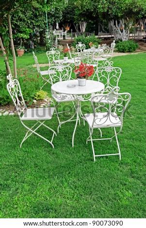 White garden furniture in beautiful garden. Vintage garden outdoor.