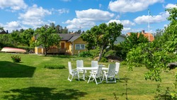 White garden furniture in relax lounge zone: table and chairs. The typical old village countryside yellow house. The cozy house in a rural area. Green lawn with fruit trees. Swings and flower beds.
