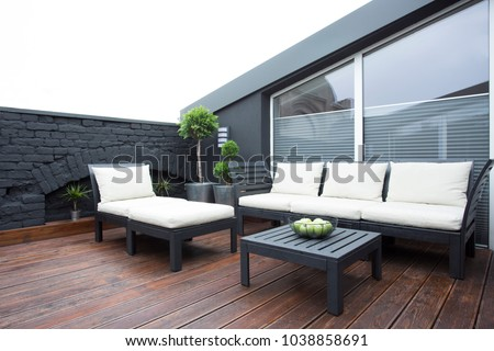 White garden furniture on the terrace with plants and dark wooden floor